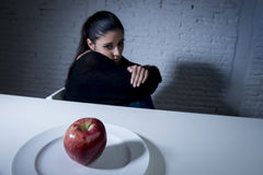 Young woman or teen looking apple fruit on dish as symbol of crazy diet in nutrition disorder Royalty Free Stock Photography