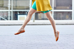 Young woman or teenage girl legs on city street. Fashion and people concept - happy young woman or teenage girl legs flying above pavement on city street Stock Photography