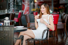 Young woman - teenage girl outdoors sitting at the cafe table wi. Th a cup of coffee and looking up stock image
