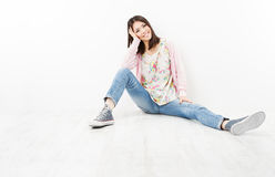 Young woman teenager in jeans sitting on white floor stock photography