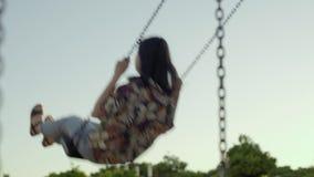 Girl swings in park stock footage