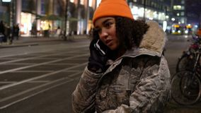 Young woman teenager talking on cell phone at night with trams by Alexanderplatz Station, Berlin, Germany. Beautiful mixed race female teenager girl young woman stock footage