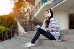 Young woman teenagers student listening music. With headphone university college outdoor with school folder and relaxing having fun enjoy or study online Royalty Free Stock Photos