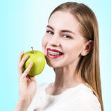 Young woman with teeth braces and green apple Royalty Free Stock Photo