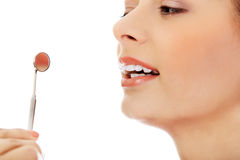 Young woman teeth and a dentist mouth mirror Royalty Free Stock Photo