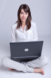 Young woman telecommuting. Barefoot young woman using her computer cross-legged on the floor royalty free stock photo