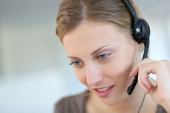 Young woman teleoperator at work. Closeup of beautiful blond teleoperator Royalty Free Stock Photo