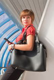 Young woman with telephone and black bag Royalty Free Stock Photo