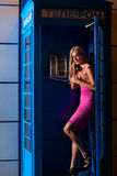 Young woman in telephone box royalty free stock photo