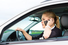 Young woman with telephone in car Stock Photography