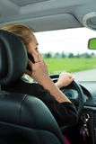 Young woman with telephone in car stock image