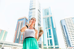 Young woman telephoning with mobile phone. Drinking coffee in metropolitan city Dubai Stock Photography