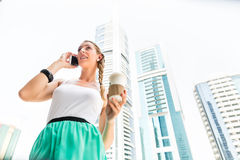 Young woman telephoning with mobile phone. Drinking coffee in metropolitan city Dubai Royalty Free Stock Image