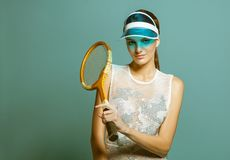 Young woman tennis player in sun visor holding tennis racquet stock photo