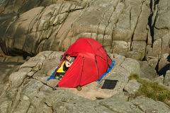 Young Woman in Tent. Young woman camping on the skerries of Southern Norway with a foldable solar panel beside the tent Stock Photos