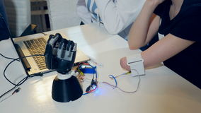 Young woman testing robotic bionic arm. Futuristic cybernetic technology in real life. stock video footage