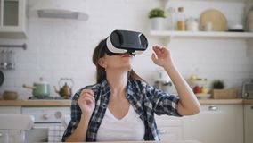 Young woman is testing virtual reality glasses in kitchen at home. stock video
