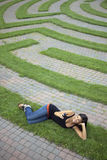 Young Woman Text Messaging in a Grass Maze Stock Photos