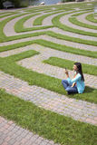 Young Woman Text Messaging in a Grass Maze Stock Photo