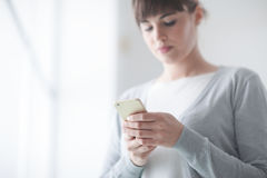 Young woman text messaging with her mobile Royalty Free Stock Images