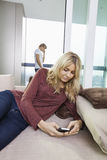 Young woman text messaging while man using cell phone in background at home Royalty Free Stock Image
