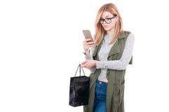 Young woman texting while carrying shopping bag Stock Photography