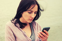 A Young Woman texting on cell phone against water , selective focus, colorized image Royalty Free Stock Photo