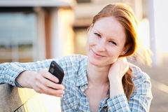 Young Woman Texting in a City at Sunset Royalty Free Stock Images