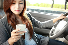Young woman texting while driving a car Royalty Free Stock Images