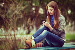 Young woman texting on her mobile phone Stock Photos