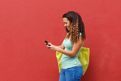 Young woman texting on mobile phone against red background Stock Image