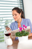Young woman texting reading newspaper cell phone Stock Images