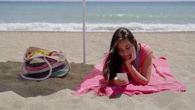 Young woman texting while relaxing on beach. Single happy young woman texting on cell phone while laying down on beach towel in shade with ocean wave in stock footage