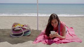 Young woman texting while relaxing on beach. Single happy young woman texting on cell phone while laying down on beach towel in shade with ocean wave in stock video footage
