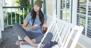 Young woman texting and sitting on porch. Outdoors Stock Images