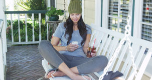 Young woman texting and sitting on porch Stock Image