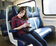 Young Woman Texting on Train. Woman texts or plays video game on mobile phone traveling  on an off peak commuter train to New York City Royalty Free Stock Photo
