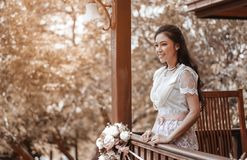 Woman in Thai traditional dress at wooden house royalty free stock images