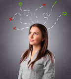 Young woman thinking with abstract marks overhead Royalty Free Stock Photos
