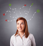 Young woman thinking with abstract marks overhead Stock Photo