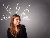 Young woman thinking with arrows overhead Stock Photography