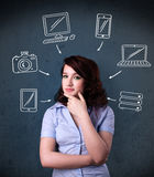 Young woman thinking with drawn gadgets around her head Stock Photo