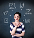 Young woman thinking with drawn gadgets around her head Royalty Free Stock Photo