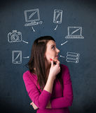 Young woman thinking with drawn gadgets around her head. Thoughtful young woman with multimedia icons around her head Royalty Free Stock Photos