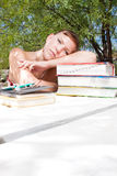A young woman thinking hard whilst studying. This attractive young lady is deep in thought in this outdoor scene Stock Photography