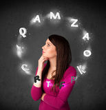 Young woman thinking with letter circulation around her head Royalty Free Stock Photos