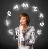 Young woman thinking with letter circulation around her head Royalty Free Stock Image