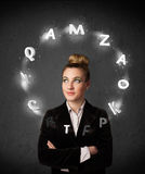 Young woman thinking with letter circulation around her head Royalty Free Stock Photography