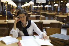 Young woman thinking in library Royalty Free Stock Photo