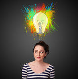 Young woman thinking with lightbulb above her head Stock Photo